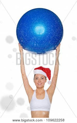 Smiley Asian Woman In Santa Cap Holds Fitball Under Snow