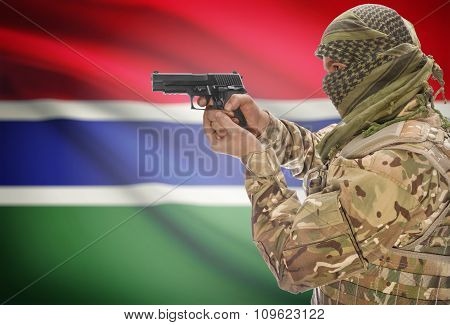 Male In Muslim Keffiyeh With Gun In Hand And National Flag On Background - Gambia