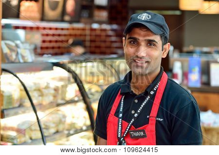 DUBAI, UAE - NOVEMBER 16, 2015: barista in Starbucks cafe in Dubai Airport. Dubai International Airport is the world's busiest airport by international passenger traffic.