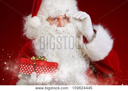 santa claus holding a gift box studio shot on red