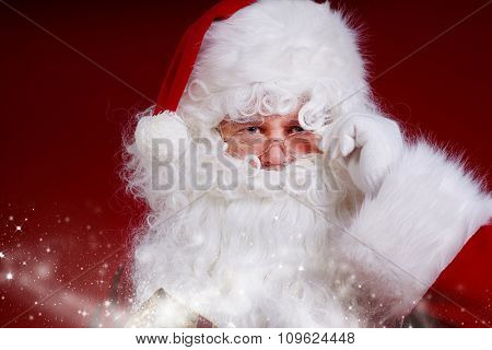 Santa Claus posing near a bag full of gifts isolated on red background