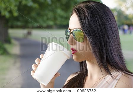 Woman drink a coffee in a park. coffee take a way. Natural and beauty woman