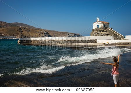 Little Girl Conducts Waves And White Church On The Beach, Andros, Greece