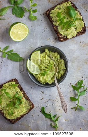 Rye Toasts With Guacamole And Arugula On Rustic  Background