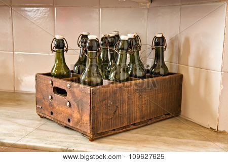 Case of Old Fashioned Bottles in Wooden Box on Counter in Kitchen