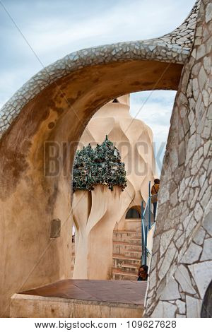 BARCELONA, SPAIN - MAY 01: View of Decorative Sculpture Detail and Staircase Through Archway on Rooftop Terrace of Antoni Gaudi Casa Mila in Barcelona, Spain on May 01, 2015