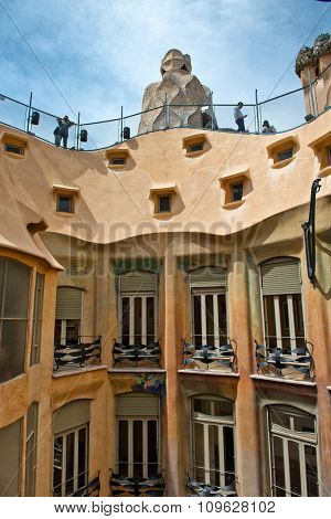 BARCELONA, SPAIN - MAY 01: View of Exterior Walls Facing Inner Courtyard with View of Barrier and Rooftop Sculptures of Casa Mila - Designed by Antoni Gaudi. May 01, 2015 in Barcelona, Spain