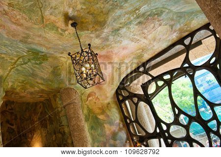 BARCELONA, SPAIN - MAY 01. Detail of Hanging Ceiling Lamp and Ornate Gate Inside Casa Mila with Painted Ceilings, Barcelona, Spaing. May 01, 2015