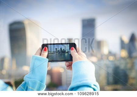 Woman taking a selfie portrait in a city. Background is city. Young woman.