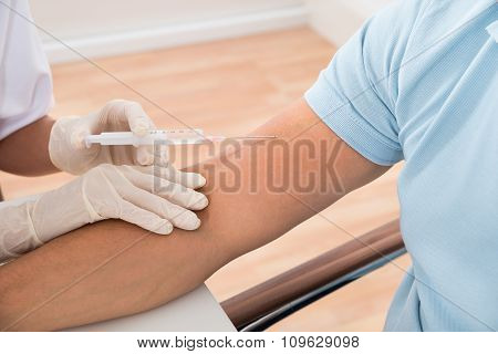 Doctor Injecting Patient With Syringe