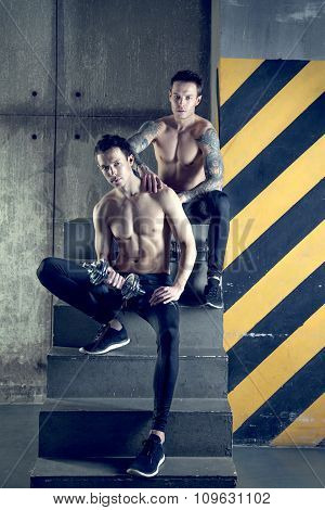 Twins muscular men working out with dumbell