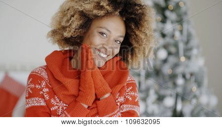 Smiling happy young African woman in a Christmas outfit with a festive red jersey and gloves standing smiling at the camera in front of a Christmas tree.