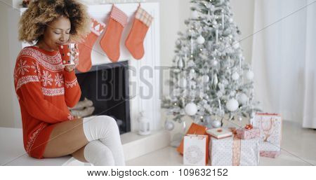 Trendy young African woman in a festive red outfit sitting enjoying a mug of hot coffee in front of the Christmas tree in her living room.