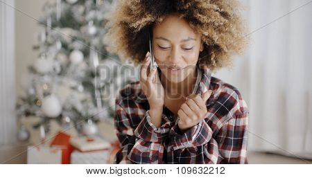 Attractive young African girl chatting on her mobile phone in front of the Christmas tree at home  natural pose