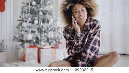 Young African woman in a trendy outfit sitting on the floor relaxing in front of the Christmas tree chatting on her mobile phone
