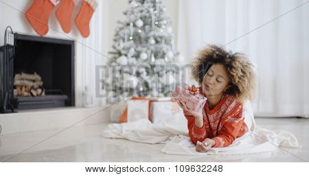 Young African girl lying on a rug in front of the Christmas tree looking at her Xmas gift with a look of anticipation and longing