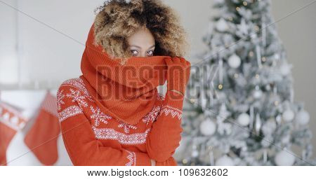 Fashionable young woman in a warm festive red woollen outfit standing in front of a decorated tree in her living room celebrating Christmas and the holiday season.