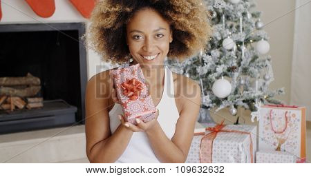 Pretty smiling young African American woman displaying a Christmas gift in her hands with a decorated tree and fireplace behind her.