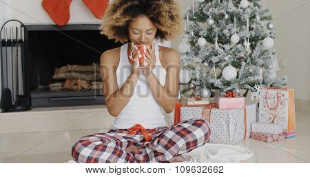 Blissful young woman holding a mug of hot coffee with a beaming smile of pleasure as she sits cross-legged in front of the Christmas tree.