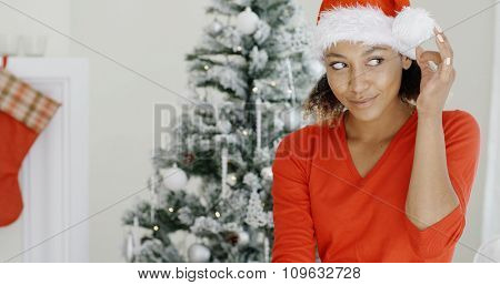 Happy festive young African woman in a Santa hat standing in front of the decorated Christmas tree looking at the camera with a friendly smile