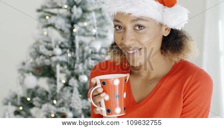 Young girl enjoying a hot refreshing cup of coffee on Christmas Day as she stands in front of the decorated tree in a Santa hat smiling at the camera.