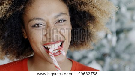 Fun young woman biting a traditional red and white striped Christmas candy cane as she looks at the camera with a mischievous smile