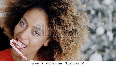 Sensuous young woman licking a red and white striped candy cane symbolic of Christmas and the holiday season as she looks at the camera with a smile  close up of her face against an Xmas tree.