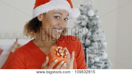 Smiling attractive African American woman wearing Santa hat holding a colorful red gift-wrapped Christmas gift displaying it to the camera