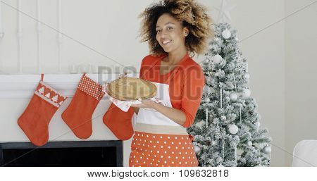 Happy trendy young woman with a Christmas dessert or pastry balanced on her hands standing in front of the decorated tree and chimney smiling at the camera.