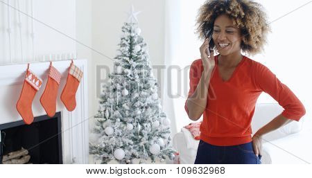 Happy young woman chatting on her mobile phone at Xmas socialising with a friend as she stands in front of the decorated Christmas tree in her living room.