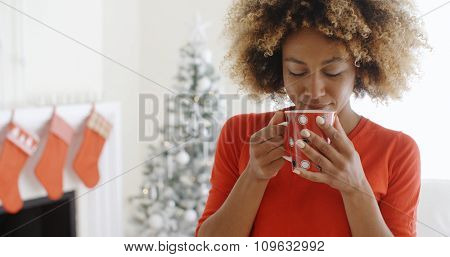 Pretty young African woman standing in front of a fireplace decorated with red Christmas stockings enjoying a mug of hot fresh coffee