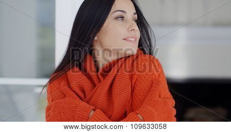 Young woman cuddling down in her warm winter fashion with a smile of pleasure and eyes closed in bliss  close up head and shoulders