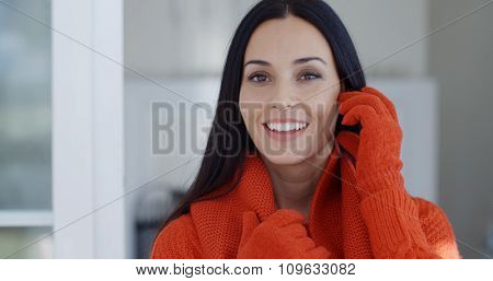 Smiling gorgeous young brunette woman in winter fashion standing indoors at home looking at the camera with a friendly happy smile