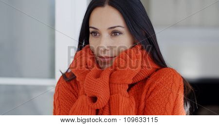 Serious attractive young woman in winter fashion standing with her gloved hands to her face as she snuggles down inside her warm woollen sweater and scarf.