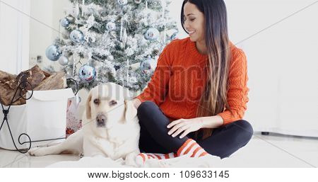Young woman and her golden labrador dog celebrating Christmas together sitting on the floor in front of the decorated tree