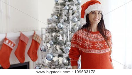 Pretty young woman celebrating Christmas at home posing in front of the decorated tree in a festive red sweater and Santa hat