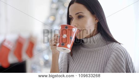 Pretty young woman enjoying a mug of refreshing coffee in her living room as she stands in front of a Christmas tree  close up head and shoulders.