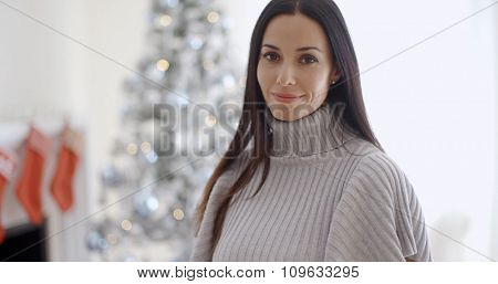 Gorgeous fashionable young woman at Christmas posing in front of the decorated tree smiling at the camera