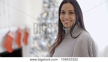 Trendy fashionable young woman wearing a winter polo neck posing in her living room at Christmas giving the camera a lovely warm friendly smile
