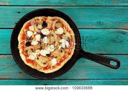 Uncooked Round Mushroom Pizza In Skillet