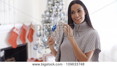 Smiling attractive trendy young woman opening a Christmas present in her living room picking at the ribbon with a look of joyful anticipation