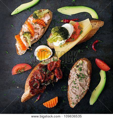 Variety of healthy sandwiches on a dark background in a rustic style.