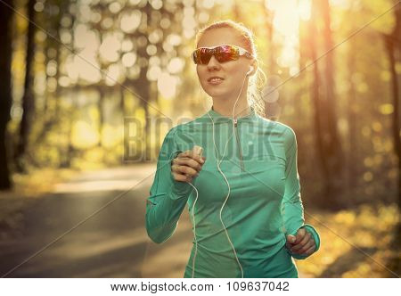 Runner in action at autumn under sunlight.