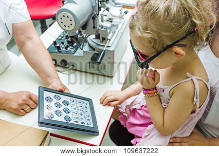 Child Is At Eye Examination In Clinic With Special Equipment.