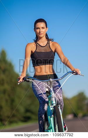 Pretty girl riding a bike in green park