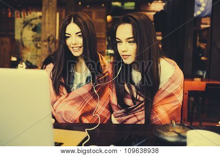 two girls watching something in laptop