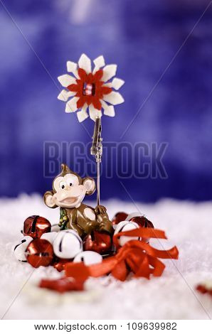 Monkey Holding A Christmas Wreath In The Hands Of A Snowflake.