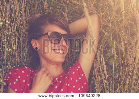 Girl relaxing in a wheat-field.