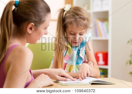Mother teaching child daughter to reading