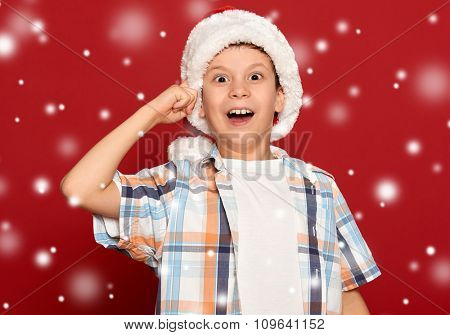winter holiday christmas concept - boy in santa helper hat have idea on red background